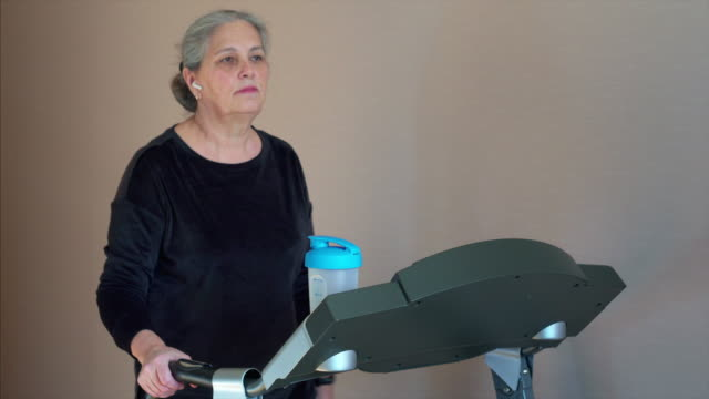 caucasian senior woman is drinking a protein shake drink. - runner rehab gym video stock e b–roll