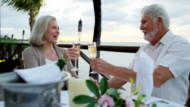 럭셔리 비치 호텔에서 저녁 식사를 즐기는 백인 노인 - rich 스톡 비디오 및 b-롤 화면