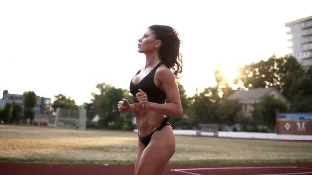vidéos et rushes de modèle sport caucasien avec beau corps en bikini noir en cours d'exécution sur la piste du stade. long cheveux brunette travaillant à l'extérieur - joggeuse