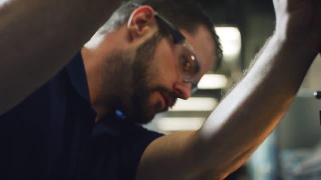 en kaukasiska tekniker i trettioårsåldern förbereder en vertikal fräs maskin för användning i en inomhus tillverkningsenhet - cnc maskin bildbanksvideor och videomaterial från bakom kulisserna