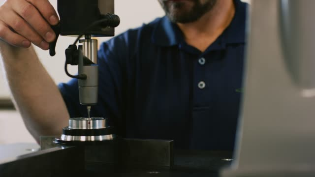 en kaukasisk tekniker i trettioårsåldern använder en koordinatmätmaskin med en ruby red torch probe för att mäta toleranser av delar i en produktionsanläggning - cnc maskin bildbanksvideor och videomaterial från bakom kulisserna