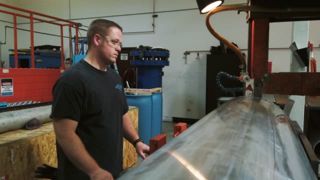 A Caucasian Technician in His Thirties Uses a Large Industrial Bandsaw to Cut Through a Spin Formed Steel Drum in an Indoor Manufacturing Facility A Caucasian Technician in His Thirties Uses a Large Industrial Bandsaw to Cut Through a Spin Formed Steel Drum in an Indoor Manufacturing Facility manufacturing occupation stock videos & royalty-free footage