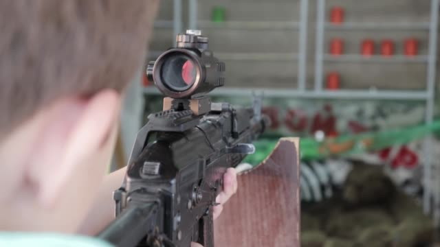 Caucasian teenage boy aiming with pneumatic rifle in shooting gallery, range