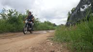 istock Caucasian tourist riding a motorbike on the wet dirt road in Asian countryside. 1284404452