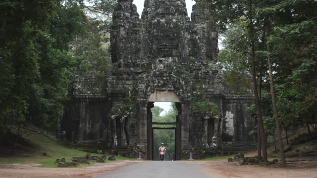 Caucasian Tourist Riding a Scooter through Cambodian Ruins video
