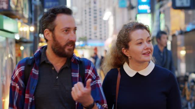 vidéos et rushes de touristes caucasiens discutant et explorant tokyo - d'ascendance européenne