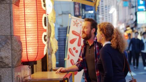 kaukasische touristen mit blick auf das menü outside restaurant in tokio - europäischer abstammung stock-videos und b-roll-filmmaterial