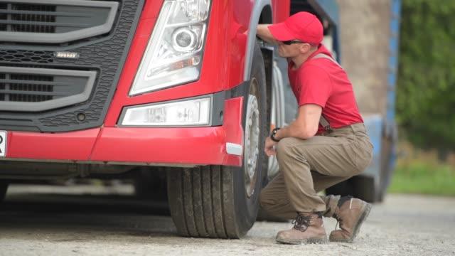 vídeos y material grabado en eventos de stock de conductor de camión caucásico haciendo comprobación rápida de neumáticos. - conductor de autobús