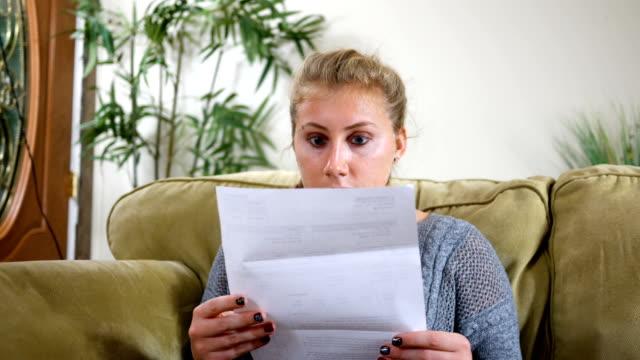 Caucasian Twenties female in shock over bill in the mail ALT