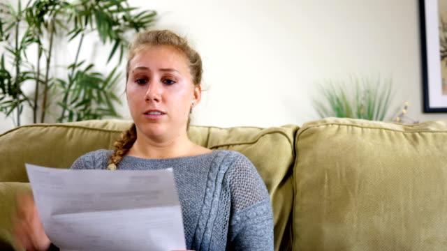 caucasian twenties female in shock over bill in the mail - długi filmów i materiałów b-roll