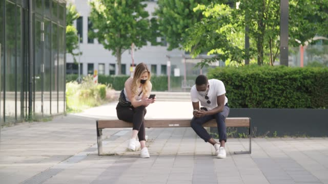 Caucasian Woman and Black Man Social Distancing on Bench