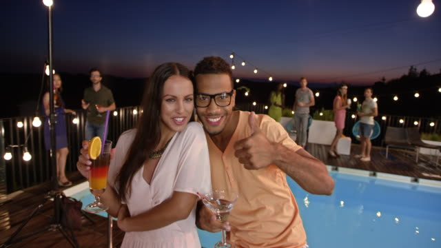 Caucasian woman and multiethnic man posing for a smartphone video at a party by the pool at night video