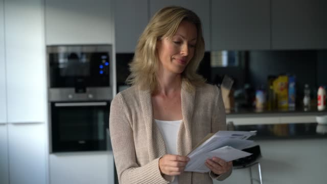 Caucasian woman at home going over her mail smiling