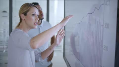 donna caucasica che discute un grafico finanziario sullo schermo in sala riunioni con il suo collega afroamericano - idea video stock e b–roll
