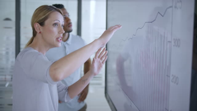 caucasian woman discussing a financial graph on the screen in meeting room with her african-american colleague - scambio d'idee video stock e b–roll