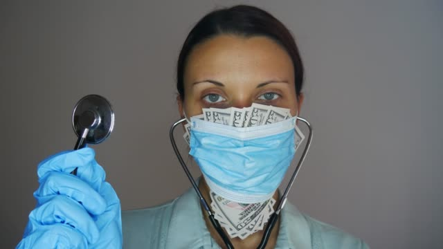 vídeos de stock e filmes b-roll de caucasian woman doctor with stethoscope and fifty-dollar bills sticking out of a medical mask on her face. corruption in medicine. - corruption