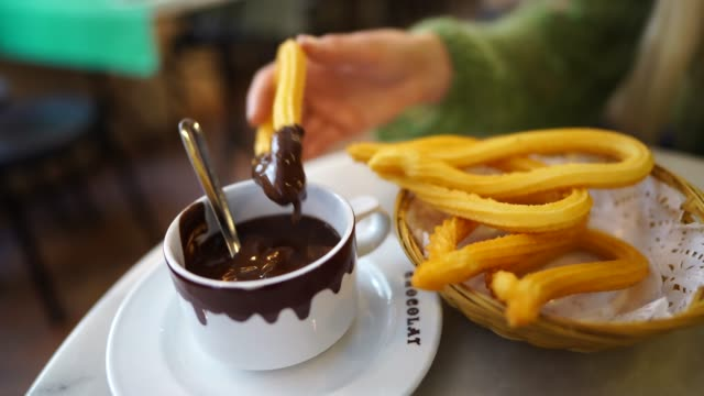 caucasian woman eats churros and chocolate at cafe  Spain video
