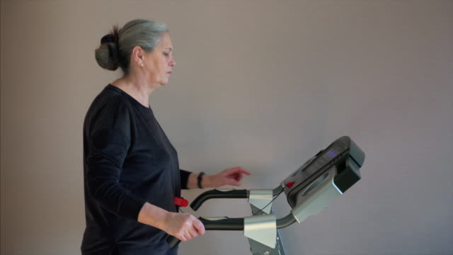 caucasian woman exercising on treadmill. she is change training mode speed. - runner rehab gym video stock e b–roll
