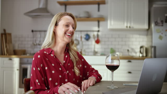 SLO MO Caucasian woman having a glass of wine at home while on a videocall