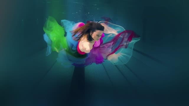 Caucasian woman in dress swimming under water video