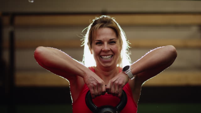 vídeos de stock e filmes b-roll de a caucasian woman in her forties wearing sports clothing lifts a kettlebell in an indoor gym while smiling and laughing - roupa desportiva