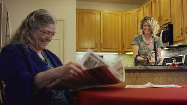 A Caucasian Woman in Her Seventies Reading a Newspaper at a Kitchen Table Smiles at and Talks with a Caucasian Woman in Her Thirties Doing Dishes at the Sink A Caucasian Woman in Her Seventies Reading a Newspaper at a Kitchen Table Smiles at and Talks with a Caucasian Woman in Her Thirties Doing Dishes at the Sink sociology stock videos & royalty-free footage
