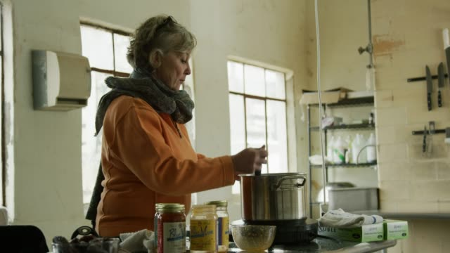A Caucasian Woman in Her Sixties Stirs Food in a Stainless Steel Saucepan in a Commercial Kitchen