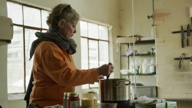 vídeos y material grabado en eventos de stock de una mujer caucásica en sus sixties stirs comida en una cacerola de acero inoxidable en una cocina comercial - receta instrucciones