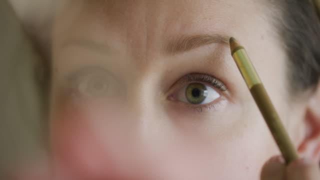 stockvideo's en b-roll-footage met een kaukasische vrouw in haar dertiger jaren gebruikt een wenkbrauw potlood om wenkbrauw poeder (make-up) van toepassing op haar wenkbrauwen - eyeliner