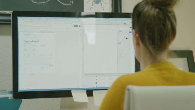 una donna caucasica sulla trentina lavora sul suo computer in un ufficio domestico al chiuso - to do list video stock e b–roll