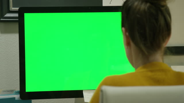 A Caucasian Woman in Her Thirties Works on Her Computer in a Home Office Indoors (Green Screen)
