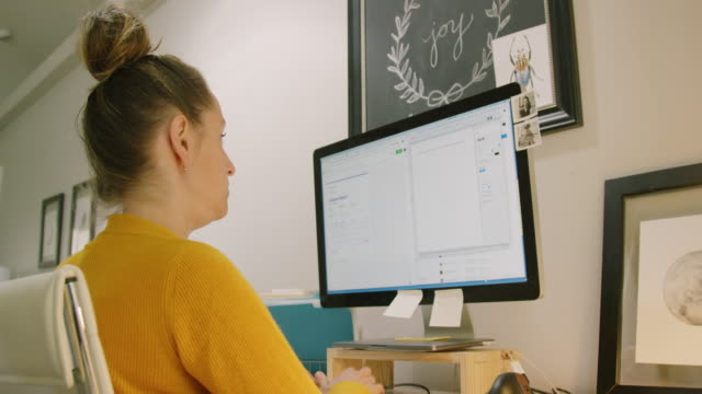 a caucasian woman in her thirties works on her computer in a home office indoors - to do list video stock e b–roll