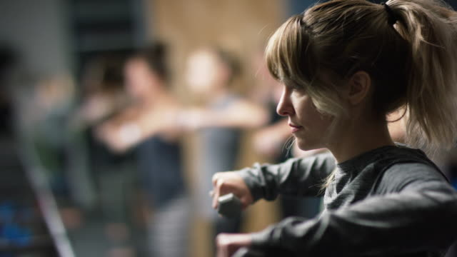 una donna caucasica sulla ventina esegue esercizi sulla spalla con pesi delle mani in una lezione di ginnastica in palestra - metodo pilates video stock e b–roll