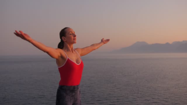 Caucasian woman in red relaxing by practicing yoga on the cliff near sea at sunset.