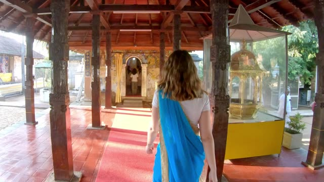 Caucasian woman is praying in Sri Dalada Maligawa temple Young girl wear traditional Saari sri lankan culture stock videos & royalty-free footage