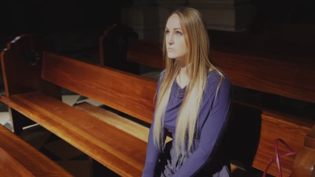 caucasian woman kneeling and praying at catholic church pew, front view video