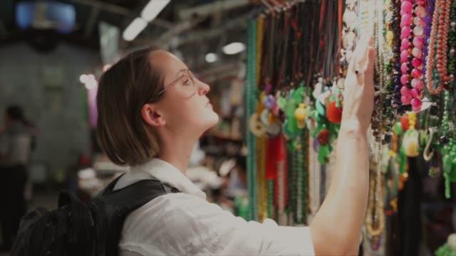 kaukasische frau auf der suche durch asiatische schmuck ständer - kurzwaren stock-videos und b-roll-filmmaterial