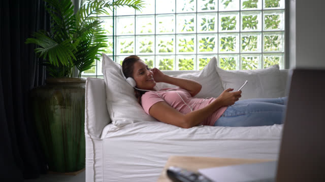 Caucasian woman lying down on couch listening music with headphones and holding her smartphone