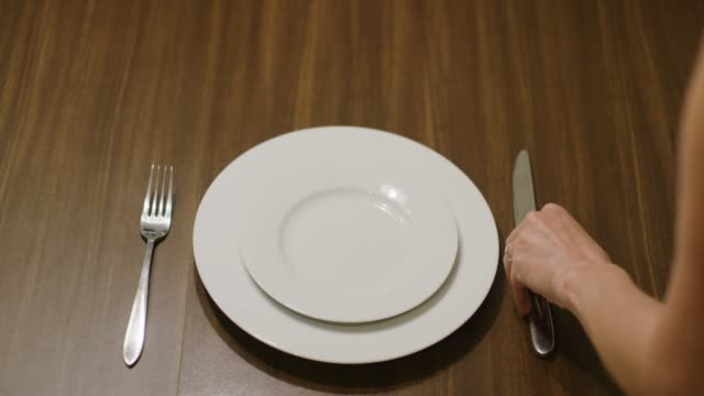 vídeos de stock e filmes b-roll de a caucasian woman places a fork, a knife, and a spoon on to a wooden table on either side of a white dinner plate with a white salad plate on top and then tops the plates with a colorful, floral cloth napkin - arranjo