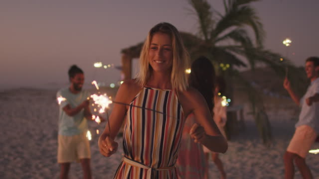 Caucasian woman playing with fire on the beach