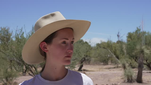 caucasian woman puts on cowboy hat in the desert