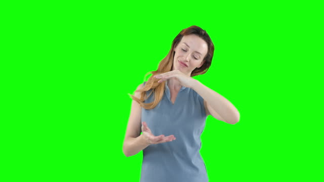 Caucasian woman raising hands on green background