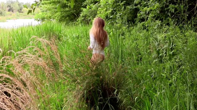 Caucasian Woman Standing In White Leotard On River Bank Blond Caucasian Woman Standing In Green Grass On River Bank In White Unitard leotard stock videos & royalty-free footage