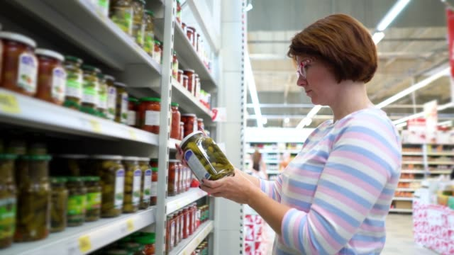 Caucasian woman standing near shop shelves and choosing pickles in grocery market Caucasian woman near shop shelves and choosing marinade pickles jar in grocery market. female customer checking product ingredients. supermarket, sale, shopping, assortment, consumerism concept pickle stock videos & royalty-free footage