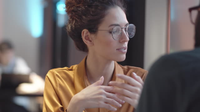 Caucasian Woman Telling Black Boyfriend about Work Problems in Cafe Over-shoulder chest-up shot of young Caucasian woman with curly hair, in glasses sitting at table in restaurant with black boyfriend and talking to him about difficult day at work gesturing stock videos & royalty-free footage