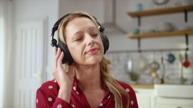 SLO MO Caucasian woman wearing headphones and listening to music at home