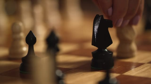 vídeos de stock e filmes b-roll de a caucasian woman with pink fingernail polish removes her opponent's knight from the board in a game of chess - xadrez