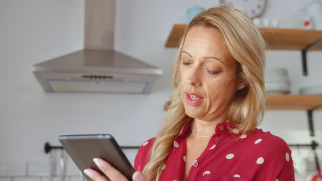 Caucasian woman working on her tablet at home while having a call