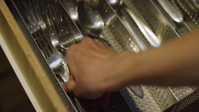 vidéos et rushes de la main d'une femme caucasienne ouvre un tiroir de cuisine, enlève une fourchette d'un organisateur d'argenterie, et ferme le tiroir - fourchette