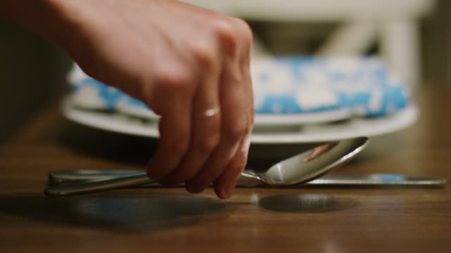 A Caucasian Woman's Hand Places a Spoon Next to a Table Knife of a Place Setting on a Wooden Table